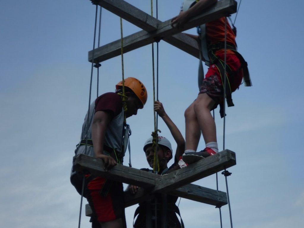 Les campeurs escaladent un parcours de cordes en hauteur